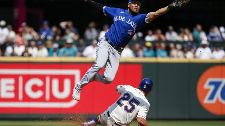 Aug 15, 2021; Seattle, Washington, USA; Toronto Blue Jays second baseman Breyvic Valera (74) catches a throw as Seattle Mariners left fielder Dylan Moore (25) steals second base during the second inning at T-Mobile Park. Mandatory Credit: Joe Nicholson-USA TODAY Sports