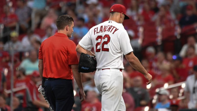 Aug 24, 2021; St. Louis, Missouri, USA; St. Louis Cardinals starting pitcher Jack Flaherty (22) leaves the field with a trainer after being pulled from the game against the Detroit Tigers during the third inning at Busch Stadium. Mandatory Credit: Joe Puetz-USA TODAY Sports