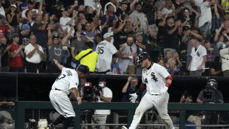 Aug 27, 2021; Chicago, Illinois, USA; Chicago White Sox catcher Yasmani Grandal (24) celebrates with third base coach Joe McEwing (47) after hitting a three-run home run against the Chicago Cubs during the third inning at Guaranteed Rate Field. Mandatory Credit: Mike Dinovo-USA TODAY Sports