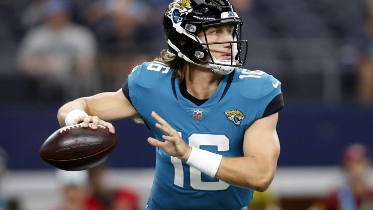 Aug 29, 2021; Arlington, Texas, USA; Jacksonville Jaguars quarterback Trevor Lawrence (16) rolls out to throw a pass in the first quarter against the Dallas Cowboys at AT&T Stadium. Mandatory Credit: Tim Heitman-USA TODAY Sports
