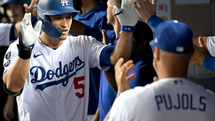 Aug 30, 2021; Los Angeles, California, USA;  Los Angeles Dodgers shortstop Corey Seager (5) is greeted in the dugout after hitting a two run home scoring left fielder AJ Pollock (11) run in the third inning of the game against the Atlanta Braves at Dodger Stadium. Mandatory Credit: Jayne Kamin-Oncea-USA TODAY Sports