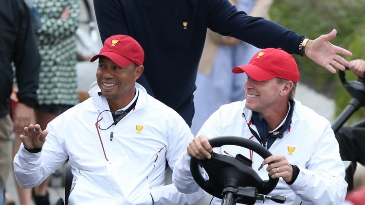 Sep 30, 2017; Jersey City, NJ, USA; (From left) Assistant captains to the U.S. team Tiger Woods and Fred Couples and Captain of the U.S. team Steve Stricker greet fans while riding in a cart during the third round foursomes matches of The President's Cup golf tournament at Liberty National Golf Course. Mandatory Credit: Bill Streicher-USA TODAY Sports