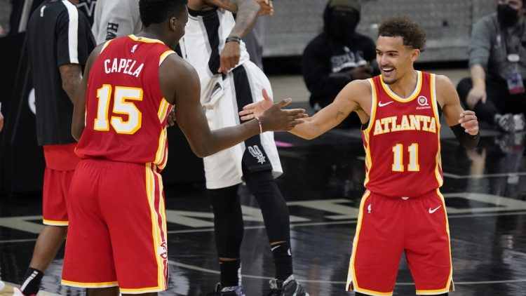 Apr 1, 2021; San Antonio, Texas, USA; Atlanta Hawks center Clint Capela (15) and guard Trae Young (11) celebrate after their double overtime victory over the San Antonio Spurs at AT&T Center. Mandatory Credit: Scott Wachter-USA TODAY Sports