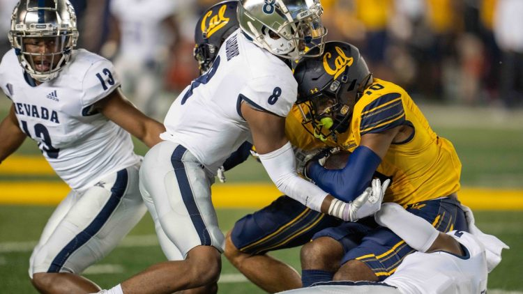 Sep 4, 2021; Berkeley, California, USA; California Golden Bears wide receiver Jeremiah Hunter (10) is tackled by Nevada Wolf Pack cornerback Isaiah Essissima (2) and defensive back JoJuan Claiborne (8) during the second quarter at FTX Field at California Memorial Stadium. Mandatory Credit: Neville E. Guard-USA TODAY Sports