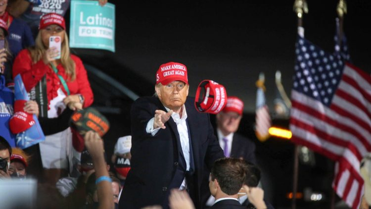 U.S. President Donald Trump tosses a Make America Great Again hat into a crowd of thousands after speaking at the Des Moines International Airport during a rally in Iowa on Wednesday, Oct. 14, 2020.  20201014 Trumpiowa