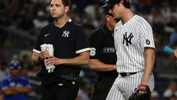 Sep 7, 2021; Bronx, New York, USA; New York Yankees starting pitcher Gerrit Cole (45) leaves the field with the trainer against the Toronto Blue Jays during the fourth inning at Yankee Stadium. Mandatory Credit: Andy Marlin-USA TODAY Sports