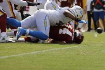 Sep 12, 2021; Landover, Maryland, USA; Washington Football Team quarterback Ryan Fitzpatrick (14) fumbles the ball after being hit by Los Angeles Chargers linebacker Uchenna Nwosu (42) while passing the ball in the second quarter at FedExField. Mandatory Credit: Geoff Burke-USA TODAY Sports