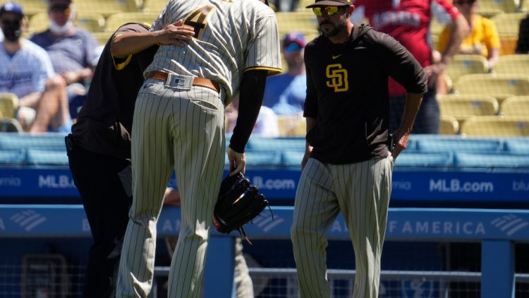 Sep 12, 2021; Los Angeles, California, USA; San Diego Padres starting pitcher Blake Snell (4) is helped off the field by a team trainer after apparently injuring himself throwing a pitch in the first inning against the Los Angeles Dodgers at Dodger Stadium. Mandatory Credit: Robert Hanashiro-USA TODAY Sports
