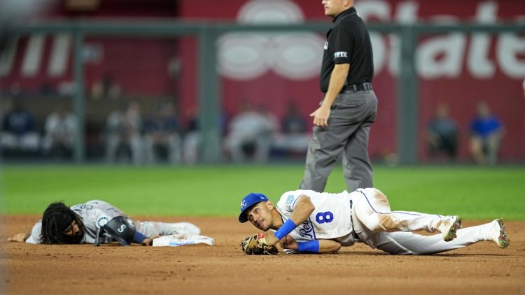 Sep 17, 2021; Kansas City, Missouri, USA; Seattle Mariners shortstop J.P. Crawford (left) reacts after he is caught stealing by Kansas City Royals shortstop Nicky Lopez (8) during the third inning at Kauffman Stadium. Mandatory Credit: Jay Biggerstaff-USA TODAY Sports