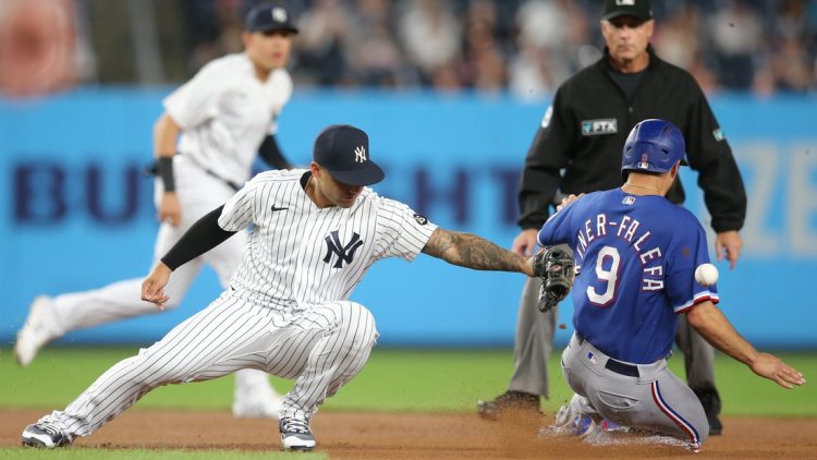 Sep 22, 2021; Bronx, New York, USA; Texas Rangers shortstop Isiah Kiner-Falefa (9) steals second base safely as the throw goes past New York Yankees second baseman Gleyber Torres (25) during the first inning at Yankee Stadium. Mandatory Credit: Brad Penner-USA TODAY Sports