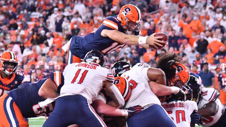 Sep 24, 2021; Syracuse, New York, USA; Syracuse Orange quarterback Garrett Shrader (16) leaps over the line of scrimmage to score a touchdown against the Liberty Flames in the second quarter at the Carrier Dome. Mandatory Credit: Mark Konezny-USA TODAY Sports