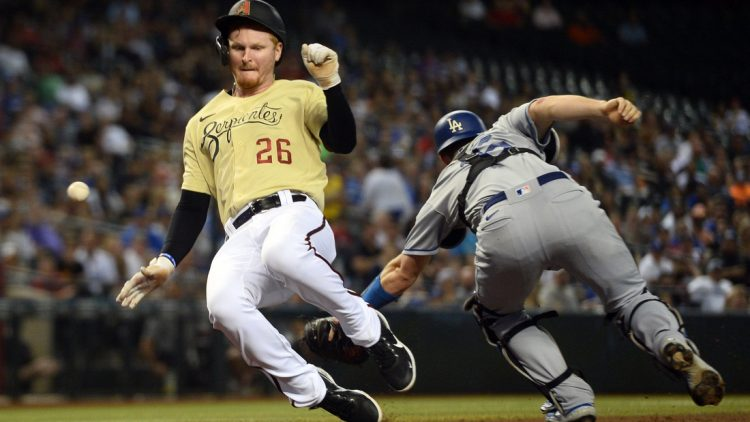 Sep 24, 2021; Phoenix, Arizona, USA; Arizona Diamondbacks first baseman Pavin Smith (26) scores a run as a throw gets away from Los Angeles Dodgers catcher Will Smith (16) during the fifth inning at Chase Field. Mandatory Credit: Joe Camporeale-USA TODAY Sports