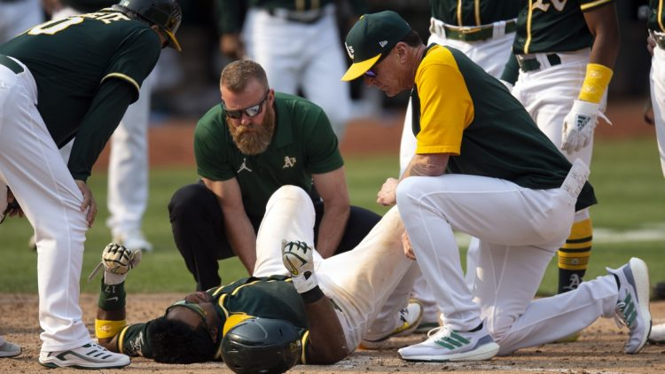 Sep 25, 2021; Oakland, California, USA; Oakland Athletics manager Bob Melvin (right) and a trainer (middle) examine Elvis Andrus after he fell to the ground with an injury while scoring the winning run against the Houston Astros during the ninth inning at RingCentral Coliseum. Mandatory Credit: D. Ross Cameron-USA TODAY Sports