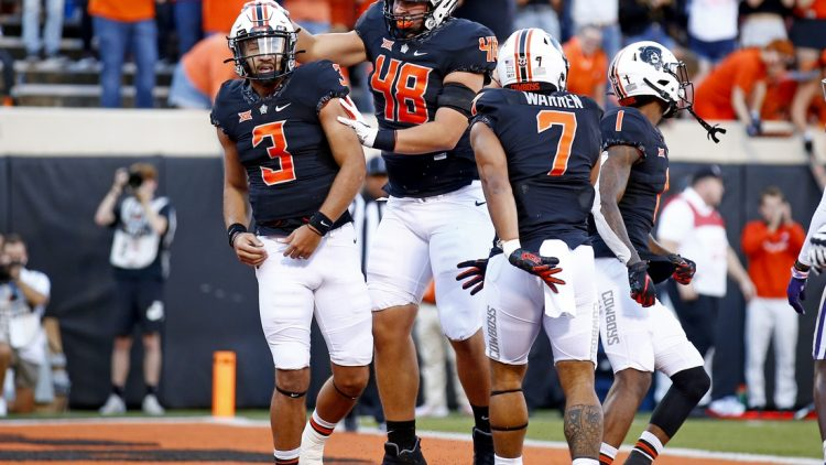 Sep 25, 2021; Stillwater, Oklahoma, USA; Oklahoma State's Spencer Sanders (3) celebrates with teammates after scoring a touchdown against the Kansas State Wildcats in the first quarter at Boone Pickens Stadium. Mandatory Credit: Sarah Phipps-USA TODAY Sports