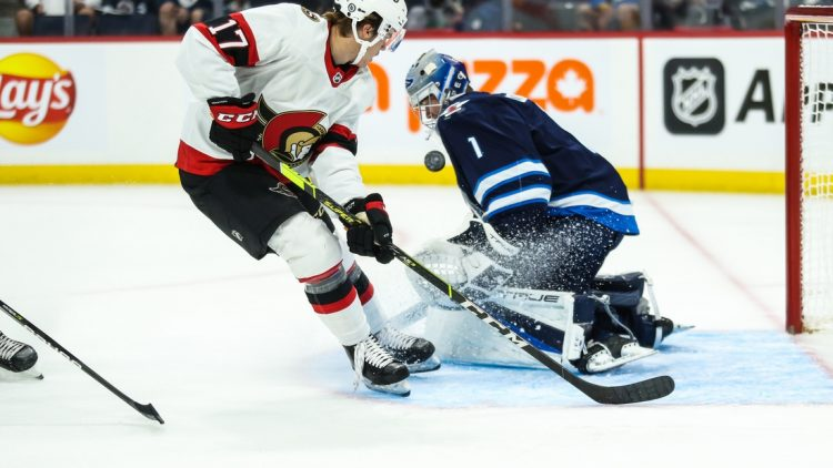 Sep 26, 2021; Winnipeg, Manitoba, CAN;  Winnipeg Jets goalie Eric Comrie (1) makes a save on Ottawa Senators forward Ridly Greig (17) during the first period at Canada Life Centre. Mandatory Credit: Terrence Lee-USA TODAY Sports