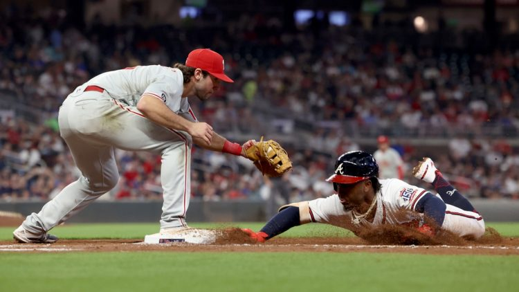 Sep 29, 2021; Atlanta, Georgia, USA; Atlanta Braves second baseman Ozzie Albies (1) slides back to first base safely on a pickoff attempt by Philadelphia Phillies first baseman Matt Vierling (19) during the third inning at Truist Park. Mandatory Credit: Jason Getz-USA TODAY Sports