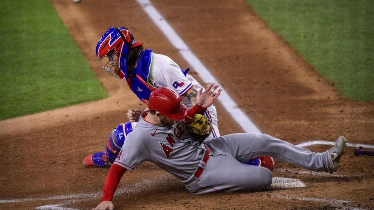 Sep 30, 2021; Arlington, Texas, USA; Los Angeles Angels left fielder Taylor Ward (3) slides safely into home plate as Texas Rangers catcher Jonah Heim (28) cannot make the tag during the first inning at Globe Life Field. Mandatory Credit: Jerome Miron-USA TODAY Sports