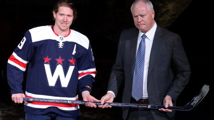 Apr 15, 2021; Washington, District of Columbia, USA; Washington Capitals center Nicklas Backstrom (19) is presented with a silver stick by Capitals' general manager Brian MacClellan (R) during a ceremony in recognition of Backstrom's 1,000th NHL game before the Capitals' game against the Buffalo Sabres at Capital One Arena. Mandatory Credit: Geoff Burke-USA TODAY Sports