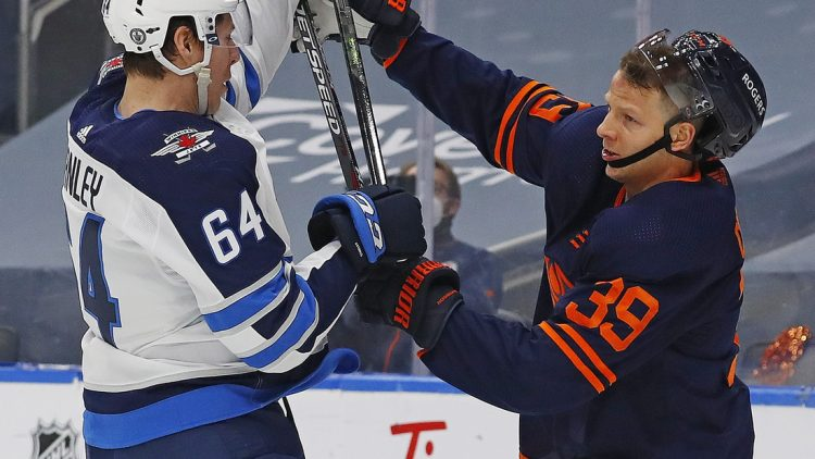 May 21, 2021; Edmonton, Alberta, CAN; Winnipeg Jets defensemen Logan Stanley (64) and Edmonton Oilers forward Alex Chiasson (39) battle for position during the first period in game two of the first round of the 2021 Stanley Cup Playoffs at Rogers Place. Mandatory Credit: Perry Nelson-USA TODAY Sports