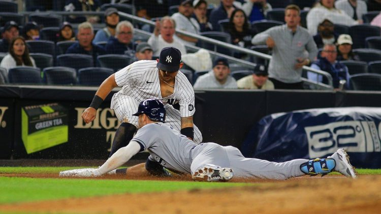 Oct 1, 2021; Bronx, New York, USA; Tampa Bay Rays center fielder Kevin Kiermaier (39) slides safely into third base with a triple against the New York Yankees during the fifth inning at Yankee Stadium. Mandatory Credit: Andy Marlin-USA TODAY Sports