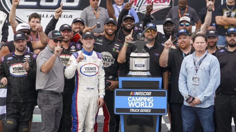 Oct 2, 2021; Talladega Speedway, AL, USA; NASCAR Gander RV and Outdoors Truck Series driver Tate Fogleman (12) holds up the number one as he poses with his team after winning the race at Talladega Speedway. Mandatory Credit: Marvin Gentry-USA TODAY Sports