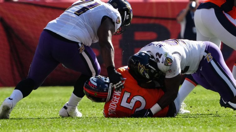 Oct 3, 2021; Denver, Colorado, USA; Baltimore Ravens defensive end Justin Madubuike (92) and defensive tackle Justin Ellis (71) tackle Denver Broncos quarterback Teddy Bridgewater (5) in the first quarter at Empower Field at Mile High. Mandatory Credit: Ron Chenoy-USA TODAY Sports