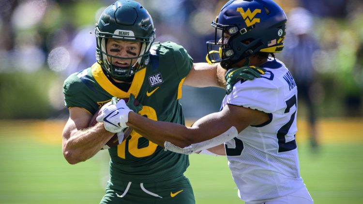 Oct 9, 2021; Waco, Texas, USA; Baylor Bears wide receiver Drew Estrada (18) stiff arms West Virginia Mountaineers safety Sean Mahone (29) during the first half at McLane Stadium. Mandatory Credit: Jerome Miron-USA TODAY Sports