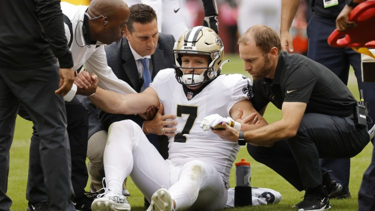 Oct 10, 2021; Landover, Maryland, USA; New Orleans Saints wide receiver Taysom Hill (7) is helped to his feet after being injured against the Washington Football Team during the second quarter at FedExField. Mandatory Credit: Geoff Burke-USA TODAY Sports