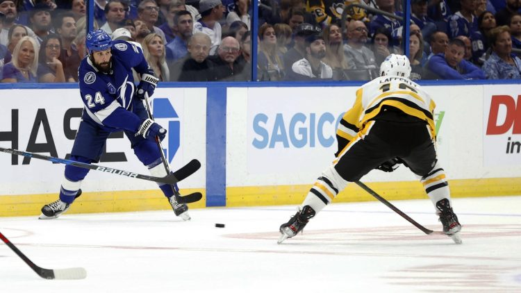 Oct 12, 2021; Tampa, Florida, USA; Tampa Bay Lightning defenseman Zach Bogosian (24) passes the puck against Pittsburgh Penguins center Sam Lafferty (18) during the first period at Amalie Arena. Mandatory Credit: Kim Klement-USA TODAY Sports